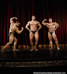 Three champion bodybuilders on stage in classic body building poses. One is flexing biceps, one is flexing abdominals, and one is showing off his shoulders. All three men are wearing only thongs. Pictures of pecs and abs.